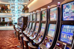 Värivalokuva, jossa peliautomaatteja siistissä rivissä oikealla puolen.
